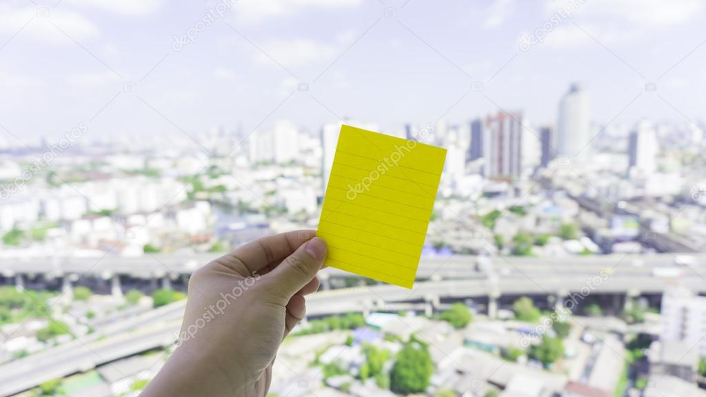 Green sticky note on hand holding with urban scene and sky