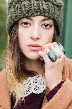 Beautiful young european woman  in beige coat, khaki hat, massive rings posing stock vector