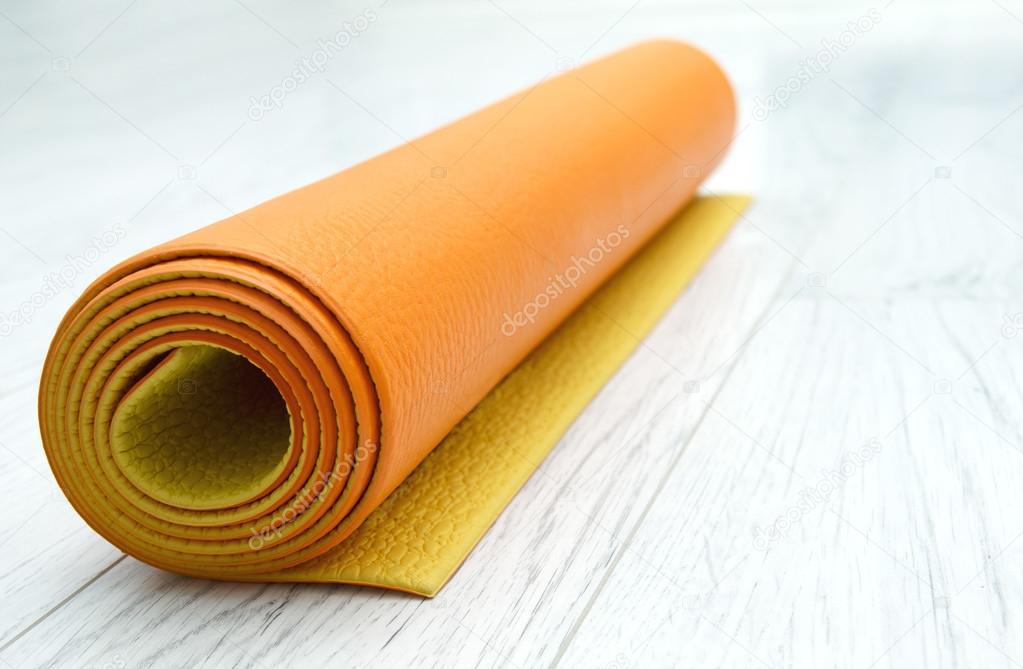 stuoia di yoga arancione brillante su un laminato grigio chiaro ...