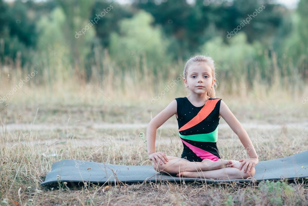 Little cute girl gymnast sits on a splits on mats in the woods