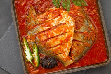 White pomfret masala curry , made in south indian style with thick red gravy and garnished with green chilli,curry leaves and malabar tamarind arranged in an iron sizzler with grey colour background.
