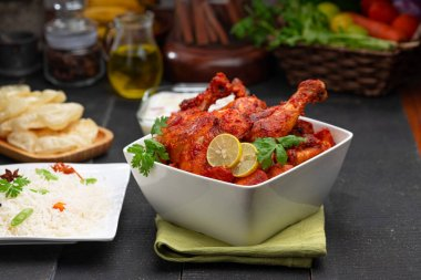 Tandoori chicken garnished with lemon and coriander leaf in square shaped white bowl with veg  pulav, raita and paapad in background with black texture,selective focus