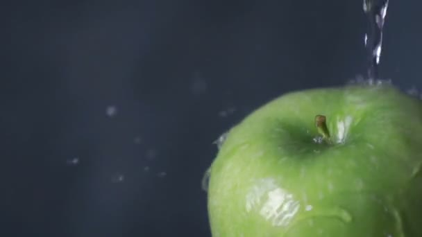 Pouring water on tasty green apple, slow motion