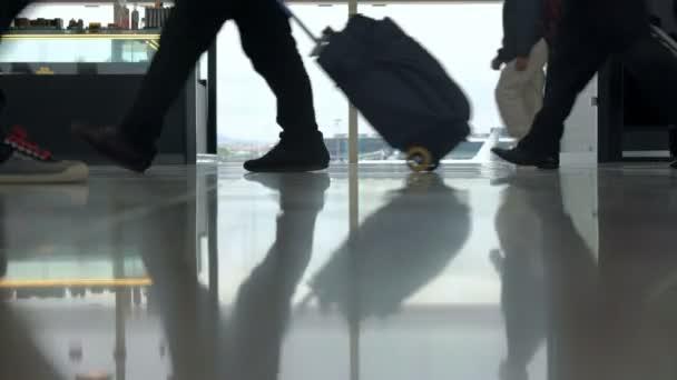 Lidé se zavazadly, procházející oknem na letišti