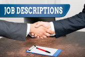 Text caption presenting Job Descriptions. Business approach a formal account of an employee s is responsibilities Two Professional Well-Dressed Corporate Businessmen Handshake Indoors