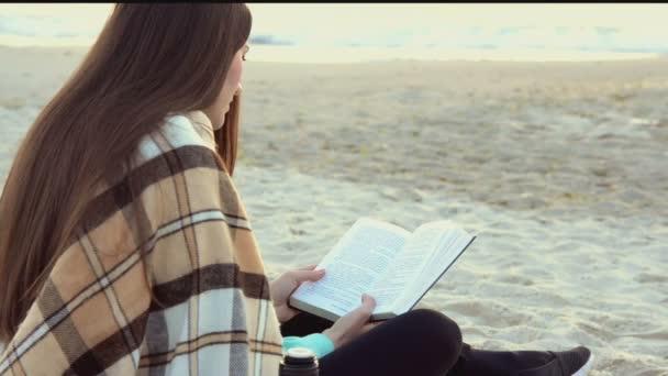 Nő könyvével a tenger közelében