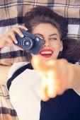 Mladá šťastná žena pokládka s staré filmové kamery