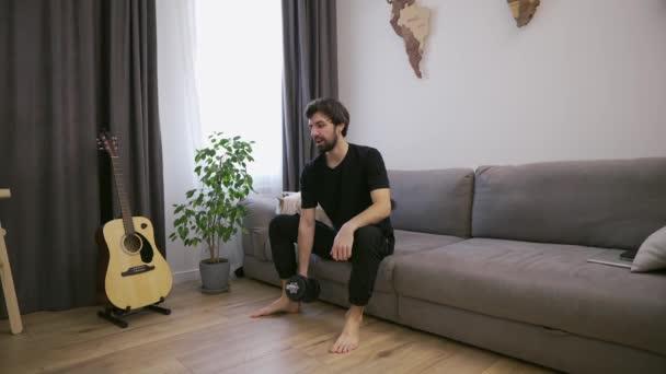 Muž dělá cvičení s činky doma v obývacím pokoji na gauči