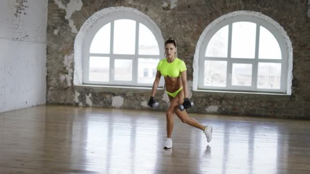 Woman doing back lunges at gym with dumbbells
