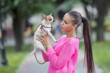 Woman holding chihuahua pet outdoors