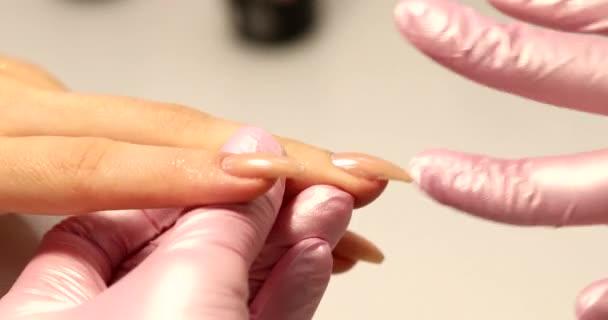 Manikérka v salónu krásy, která vtírá olej do rukou klienta. Profesionální koncept péče o nehty. Práce specialisty zblízka.