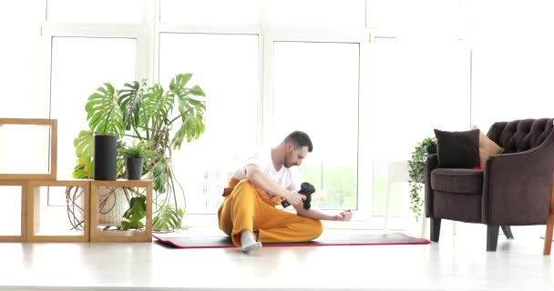 Sportovní sportovec masírující tělo ruční masážní pistolí při cvičení doma