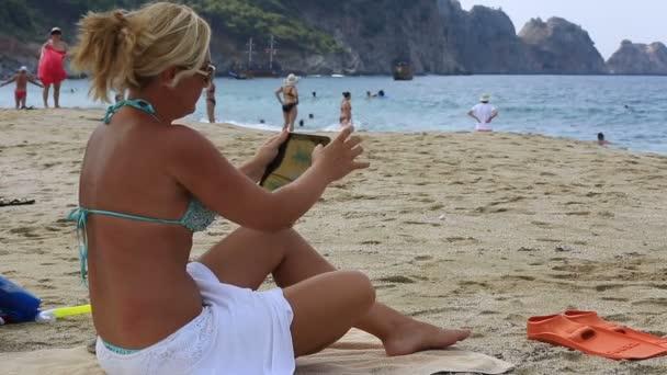 atraktivní blond ženy pomocí digitálních tabletu