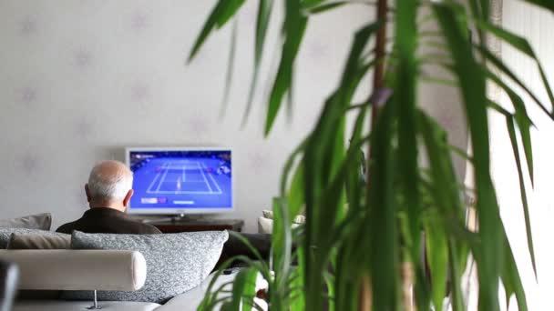 Starší muž sledování televize, sledování tenis