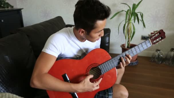 atraktivní mladík hraje kytara