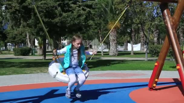 Portrait of a cute girl swinging at the playground