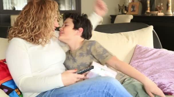 Roztomilý chlapec nabízí dárek k matce v obývacím pokoji
