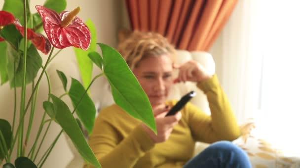 Caucation, blond středního věku žena sedí na pohovce v obývacím pokoji, sledování televize
