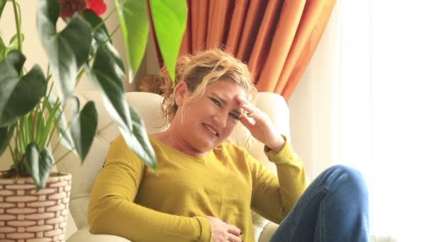 Krank, schmerzhafte Frau auf einem Sofa sitzend und mit Bauchschmerzen