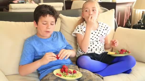Roztomilý dívka a chlapec jíst jahody