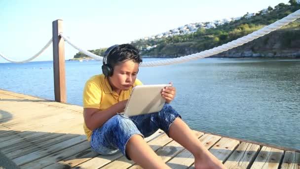 Chlapec hrát digitální tabletový počítač na dřevěném molu u moře