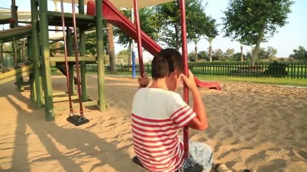 Smutný malý chlapec na hřišti
