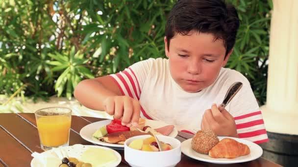 Kind frühstückt im Garten