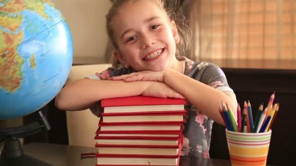 Elemi kor lány pózol egy halom könyvet a
