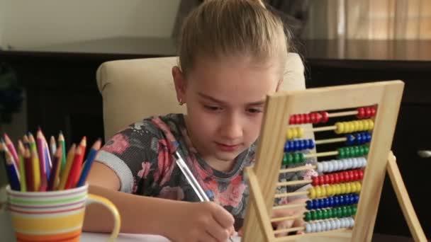 Kislány tanulmányi otthon és mosolyogva a kamera