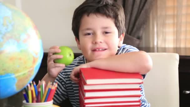 Elementary age boy posing on a stack of books.