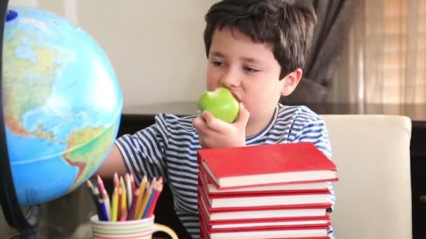 Elemi kor fiú pózol a verem a könyvek
