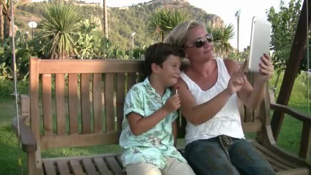Matka a syn sedí na houpačce a s ohledem selfie