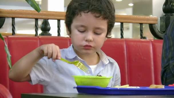 Malý chlapec v fast food restaurace