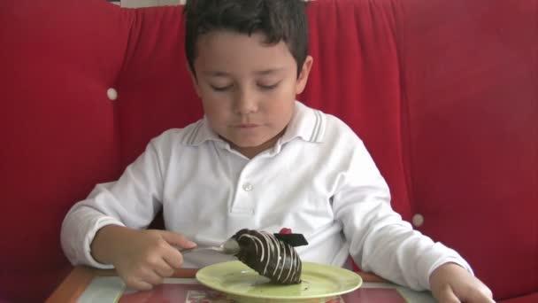 dítě jíst koláče a úsměv do kamery