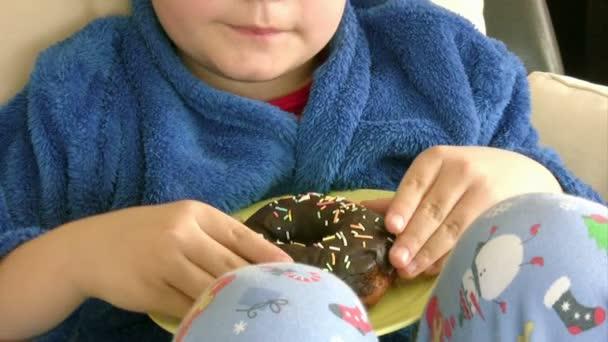 Chlapec má rád čokoládové koblihy