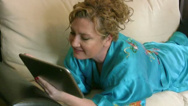 Žena leží na pohovce v obývacím pokoji a použití digitálních tabletu