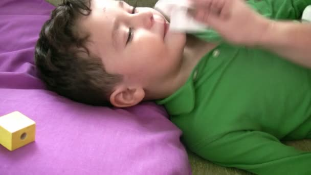 Sick child  lying in bed with a thermometer