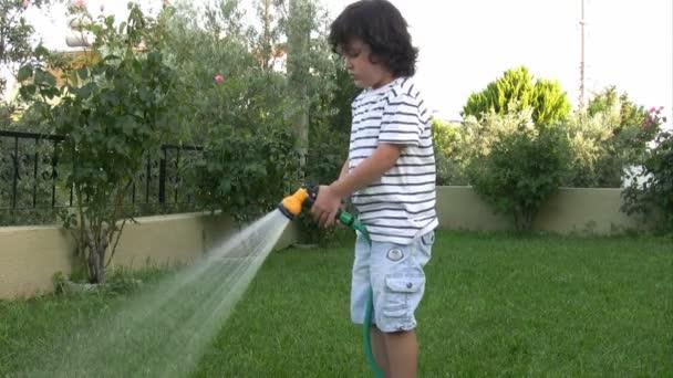 Malý chlapec zavlažování zahrady