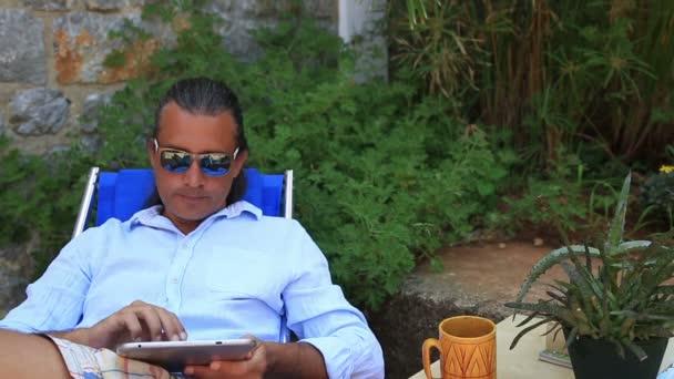 Člověk s použitím digitálního tabletu v zahradě