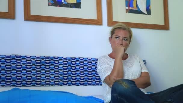 smutná žena sedí na posteli