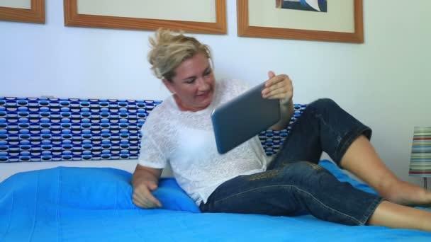 Žena leží na posteli a sledování filmu