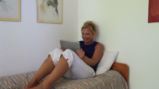 žena ležela a sledování videa v tabletovém počítači
