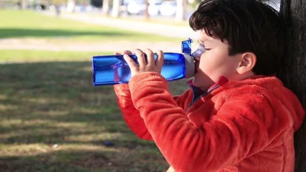 Porträt eines niedlichen Kindes, das Wasser aus einer Flasche im Freien trinkt