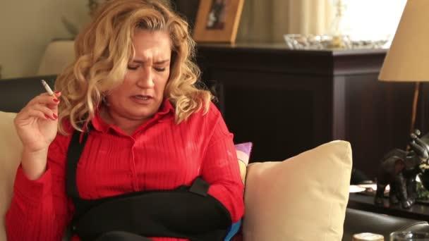 Fájdalmas nő ül a kanapén és a cigaretta a dohányzás
