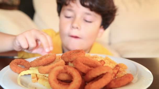 Dítě jí křupavé smažené cibulové kroužky a hranolky