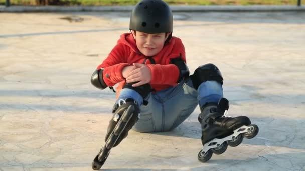 Zraněný chlapec spadl do brusle, sedí na podlaze