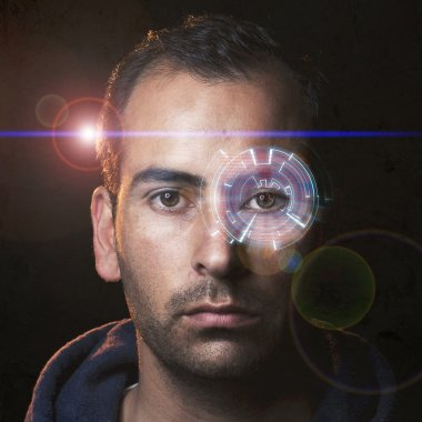 Futuristic portrait of a young man with a hologram in one eye and movie like lens flare