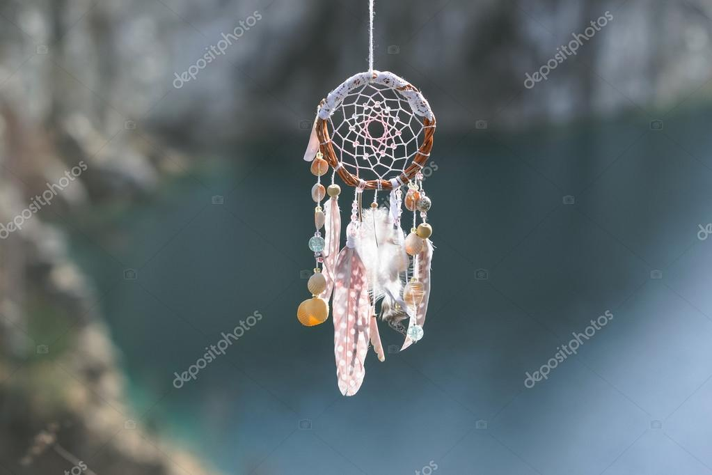 Handmade native american dream catcher on background of rocks an