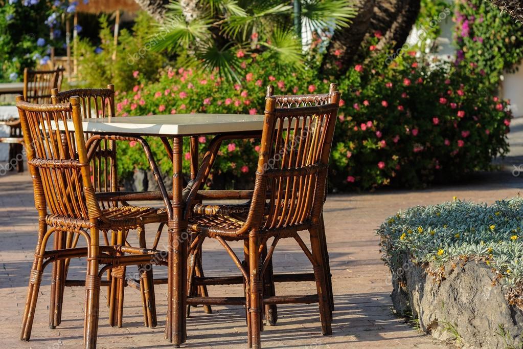 Tavoli e sedie di vimini con ombrelloni di paglia nel ristorante