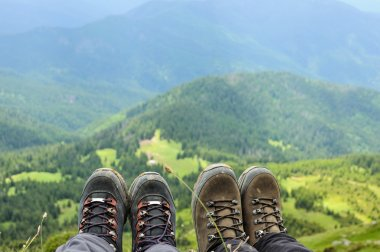 Hiking boots of traveler sitting on high mountain top